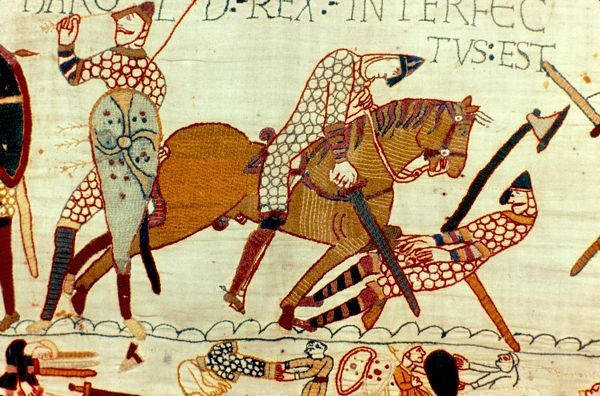 Bayeux Tapestry 1067: Battle of Hastings, 14 October 1066. The death of Harold II, last Anglo-Saxon king of England. Left, figure pulling arrow from eye and then being cut down by Norman knight. Armour Chain Mail Sword Axe Textile