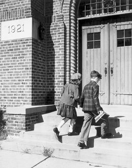 Two children walking into school