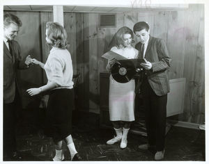 Couple dancing another looking at record album
