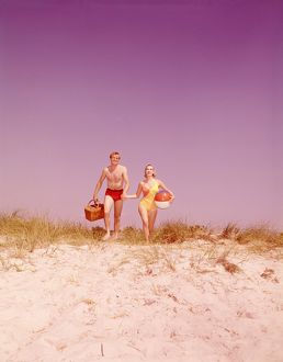 Couple with picnic basket and ball walking on beach