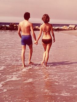 Couple from behind walking on beach