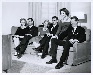 Three couples watching television together