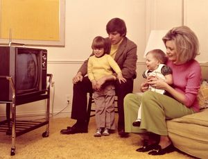Family watching TV in 1970's home
