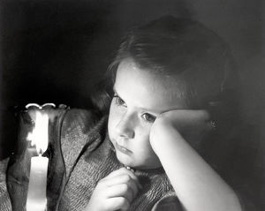 Girl looking at lighted candle
