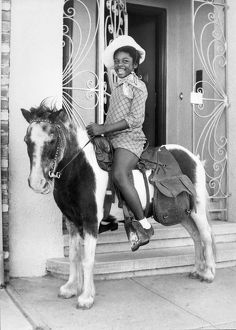 A very happy African American girl on a pony
