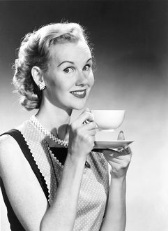Housewife in pearls and apron drinks coffee