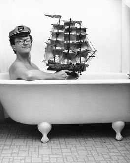 Man in captain hat holding toy ship in bathtub