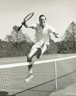 Man holding tennis racquet leaping over tennis net, 1950-60s, black and white
