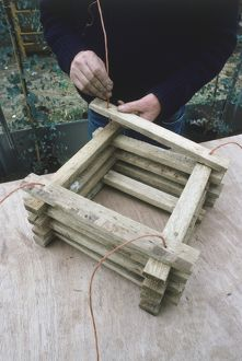 Man making a wooden hanging basket, adding the last strut.
