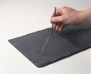 Man using large iron nail to scratch line on slate