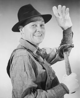 Portrait of carpenter waving and holding hammer