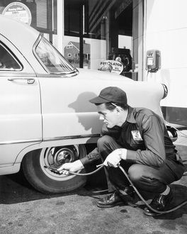 Service man replacing air in car tire