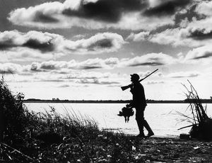 Silhouette of duck hunter walking along lake