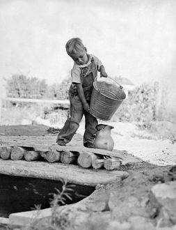 A small boy on a farm pours water from a bucket into a pitcher for the house.