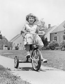 Smiling girl on tricycle
