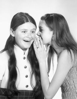 Teen girl sharing a secret with her friend