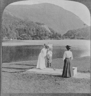 Woman and boy with golf clubs in foreground, 2 people in boat on lake, mountain in
