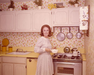 Woman preparing food in kitchen of 1970s home