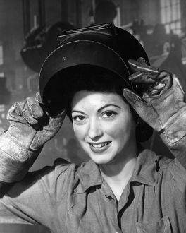 Woman wearing welding mask and gloves in wartime